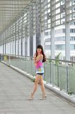 Beautiful Asian girl showing youthful vigor on the pedestrian bridge. Sweet smile, hot body, sexy, youthful, unrestrained Stock Images