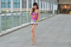 Beautiful Asian girl showing youthful vigor on the pedestrian bridge. Sweet smile, hot figure, sexy, youthful, unrestrained Stock Images