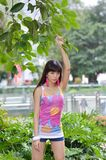 Beautiful Asian girl shows her youth in the park. Sweet smile, hot figure, sexy, youthful, unrestrained,long legs, high heels Stock Image