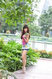 Beautiful Asian girl shows her youth in the park. Sweet smile, hot figure, sexy, youthful, unrestrained,long legs, high heels Royalty Free Stock Photos