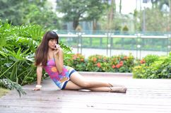 Beautiful Asian girl shows her youth in the park. Sweet smile, hot figure, sexy, youthful, unrestrained,long legs, high heels Royalty Free Stock Images