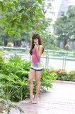 Beautiful Asian girl shows her youth in the park. Sweet smile, hot figure, sexy, youthful, unrestrained,long legs, high heels Royalty Free Stock Image