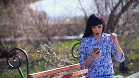 A beautiful asian girl sits in a park on a bench, reads a message on the smartphone and is very surprised, shouts wow stock footage