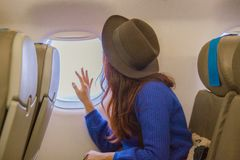 Young asian woman traveler looking view at window in airplane with happiness and relaxing stock image