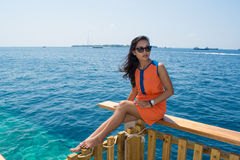 Beautiful asian girl sitting near ocean. At Maldives Royalty Free Stock Photo