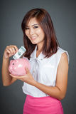 Beautiful Asian girl smile put a bill to pink pig money box Stock Photography