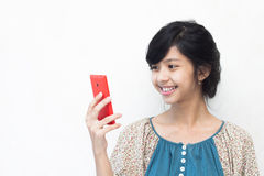Beautiful asian girl smiling at her smartphone Royalty Free Stock Photography