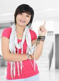 Beautiful Asian girl smiling and pointing. At the room Royalty Free Stock Photos