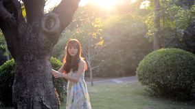 Beautiful asian girl smiling in the sunshine. Trees, sunlight, meadow, bushes, dress stock video