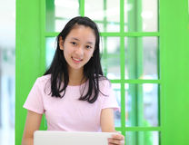 Beautiful asian girl smiling and using laptop computer . Stock Photo