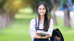 Beautiful Asian girl student holding books and smiling at camera royalty free stock images