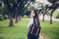 Beautiful Asian girl student holding books and smiling at camera. And learning and education concept  on park in summer for relax time at sunset with a warm Royalty Free Stock Images