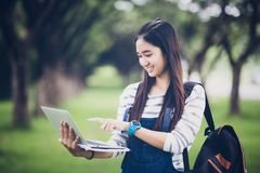 Beautiful Asian girl student holding books and smiling at camera. And learning and education concept  on park in summer for relax time at sunset with a warm Royalty Free Stock Photography