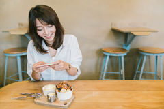 Beautiful Asian girl taking photo of chocolate toast cake, ice-cream, and milk at coffee shop. Dessert or food photograph hobby. Smartphone or mobile phone stock photo