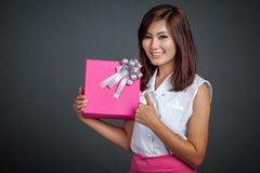 Beautiful Asian girl thumbs up with a gift box Stock Photography