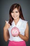 Beautiful Asian girl thumbs up with a pink pig money box Stock Photos