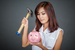 Beautiful Asian girl about to hit money box with hammer Royalty Free Stock Images