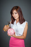 Beautiful Asian girl about to hit money box with hammer Royalty Free Stock Photo