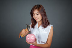 Beautiful Asian girl about to hit money box with hammer Royalty Free Stock Photography