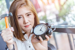Beautiful asian girl try to hit black alarmclock Royalty Free Stock Image