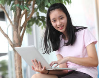 Beautiful asian girl using laptop computer. Stock Image