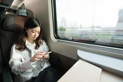 Beautiful asian girl using smartphone while travelling on the train, communication concept. Royalty Free Stock Photo