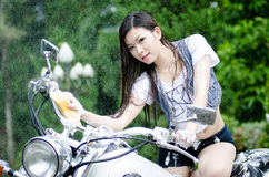 Beautiful Asian girl is washing big bike Royalty Free Stock Photography