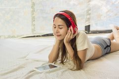 Beautiful Asian girl wearing headphones, listening to music in bedroom, morning with soft sunlight, with concept of relaxation and stock photography
