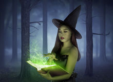 Beautiful asian girl wearing witch cloth reading spell in the bo Stock Photo