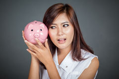 Beautiful Asian girl wonder how much money in pig money box Royalty Free Stock Image