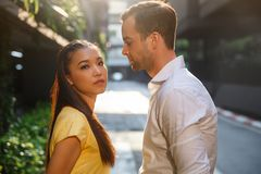 Asian girl and caucasian man together on the street royalty free stock photo