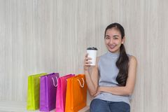 Beautiful Asian girl, young shopper, colorful paper bag and coffee cup royalty free stock photography