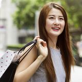Beautiful asian girls with shopping bags. Royalty Free Stock Image