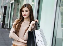 Beautiful asian girls with shopping bags. Royalty Free Stock Images