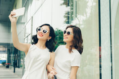 Beautiful asian girls with shopping bags taking selfie photo at royalty free stock photo