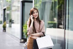 Beautiful asian girls with shopping bags using smartphone Stock Photography