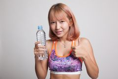 Beautiful Asian healthy girl with bottle of drinking water. Beautiful Asian healthy girl with bottle of drinking water on gray background Royalty Free Stock Image