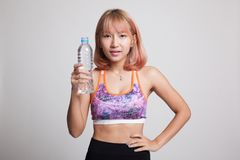 Beautiful Asian healthy girl with bottle of drinking water. Beautiful Asian healthy girl with bottle of drinking water on gray background Royalty Free Stock Images