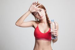 Beautiful Asian healthy girl with bottle of drinking water. Beautiful Asian healthy girl with bottle of drinking water on gray background Stock Photos