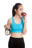 Beautiful Asian healthy girl with clock and apple Stock Image