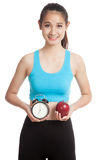 Beautiful Asian healthy girl with clock and apple Royalty Free Stock Images