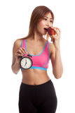 Beautiful Asian healthy girl with clock and apple Stock Images