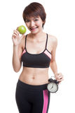 Beautiful Asian healthy girl with clock and apple. Royalty Free Stock Image