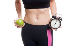 Beautiful Asian healthy girl with clock and apple. Stock Photo