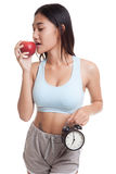 Beautiful Asian healthy girl with clock and apple. Royalty Free Stock Photos