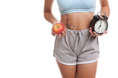 Beautiful Asian healthy girl with clock and apple. Stock Photography