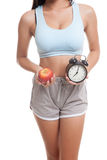 Beautiful Asian healthy girl with clock and apple. Royalty Free Stock Images