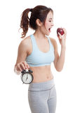 Beautiful Asian healthy girl with clock and apple. Stock Image