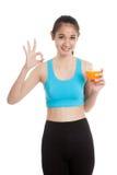 Beautiful Asian healthy girl drinking  orange juice show OK sign Stock Photos