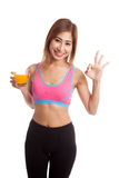 Beautiful Asian healthy girl drinking  orange juice show OK sign Royalty Free Stock Images